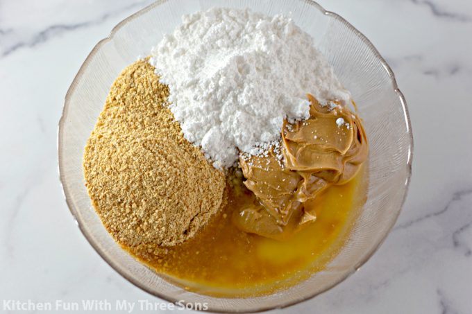mixing together graham cracker crumbs, melted butter, peanut butter, and powdered sugar