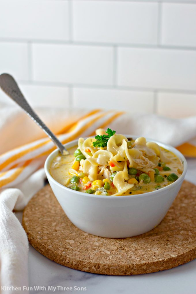 Chicken Pot Pie Noodles in a white bowl with a spoon