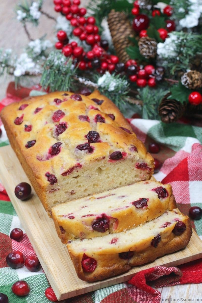 Orange Cranberry Bread with snow frosted decorations behind it.