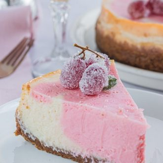 Pink Champagne Cheesecake with frosted grapes on a white plate