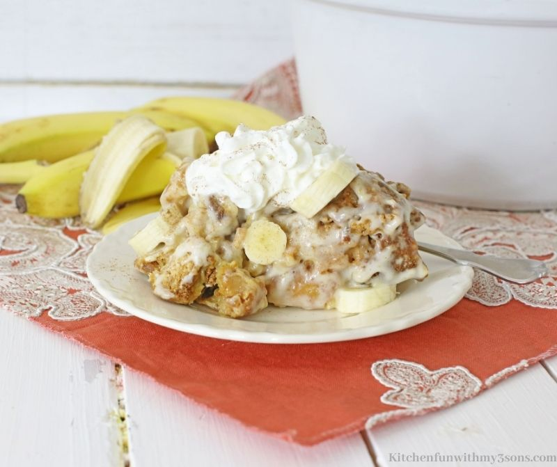 Banana Cream Slow Cooker Bread Pudding on a serving plate with bananas in the back.