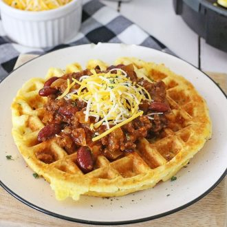 Chili and cheese on top of cornbread waffles on a white plate