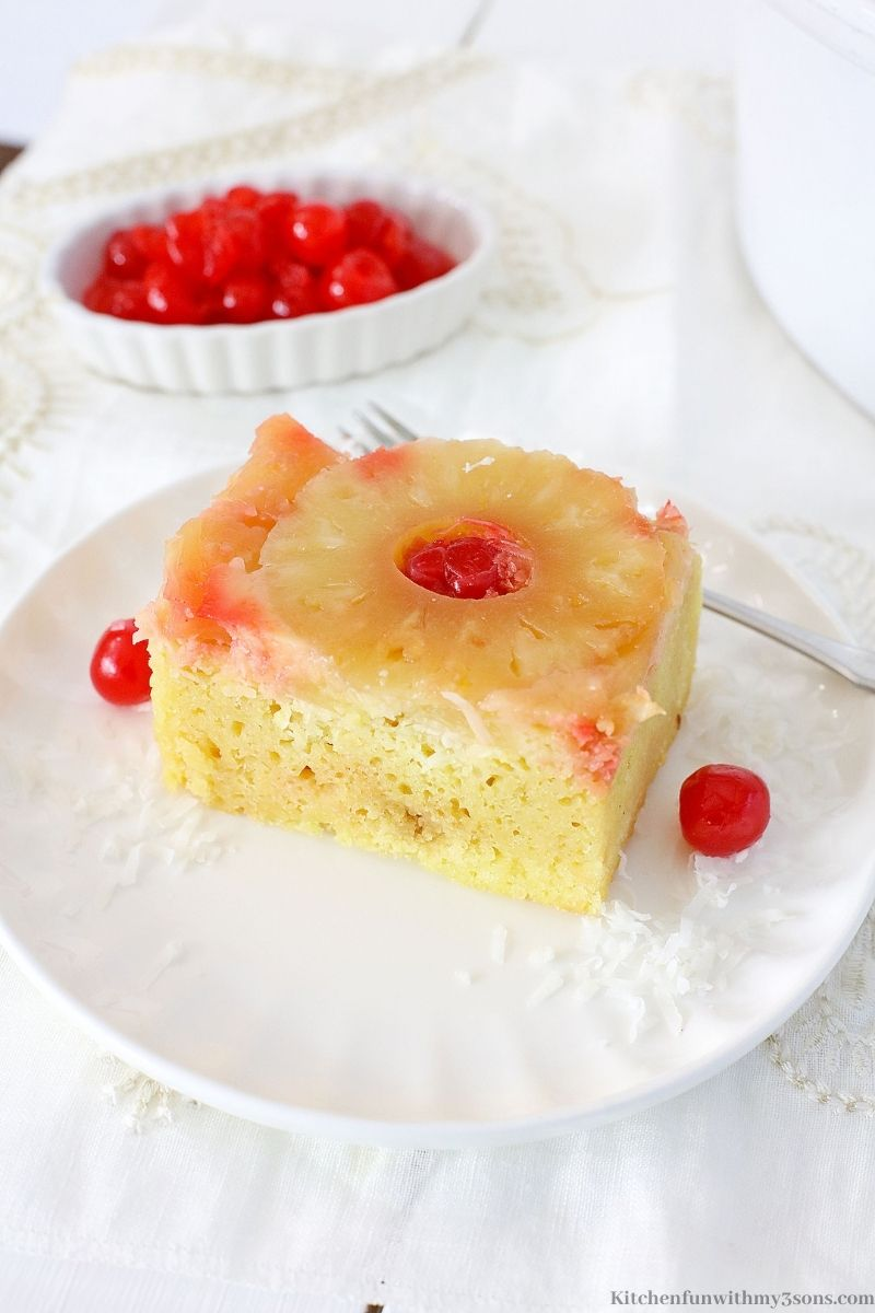 Crock-Pot Pineapple Upside Down Cake with a fork and extra cherries on the side.
