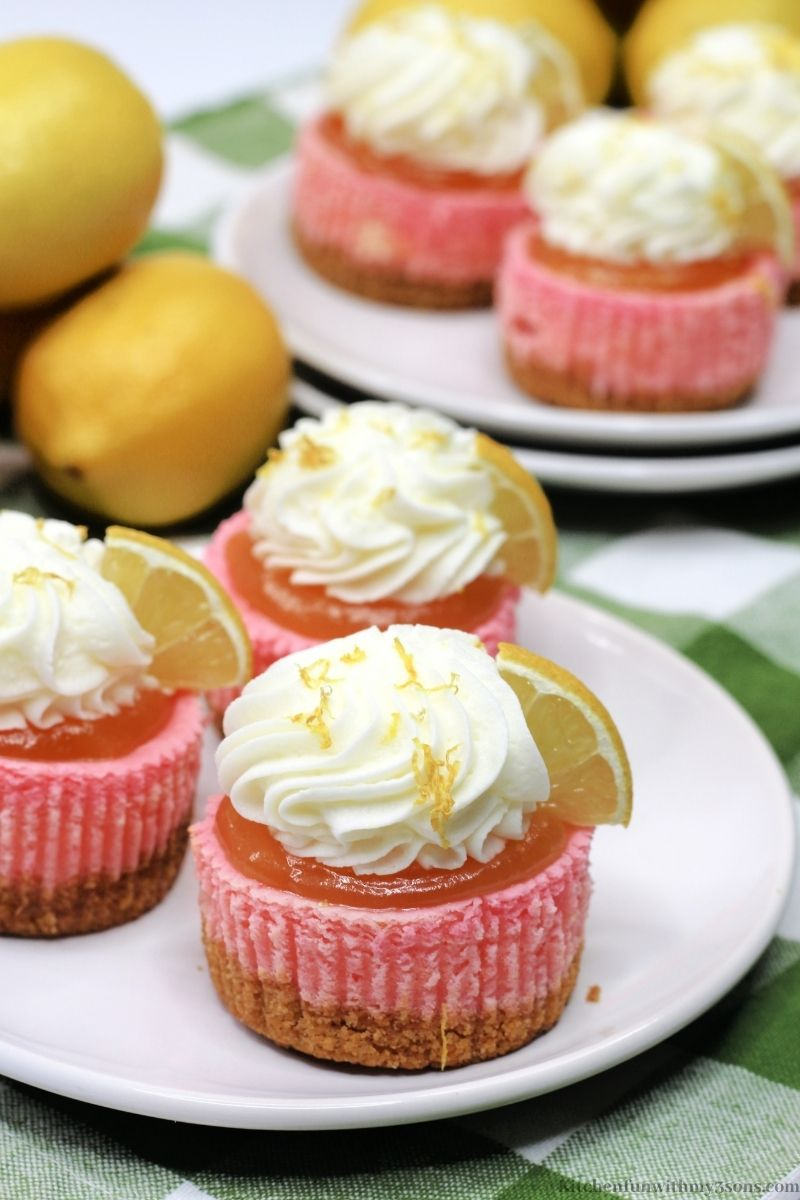 Pink Lemonade Mini Cheesecake topped with lemon zest and a lemon wedge.