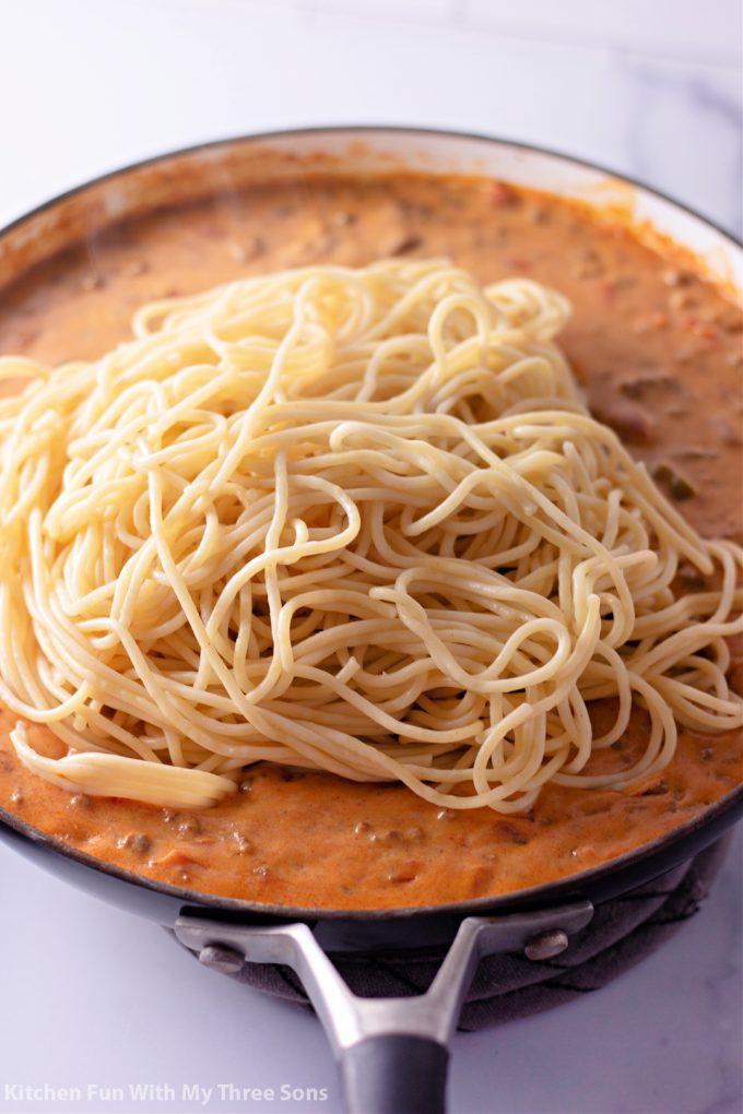 adding spaghetti to the taco sauce