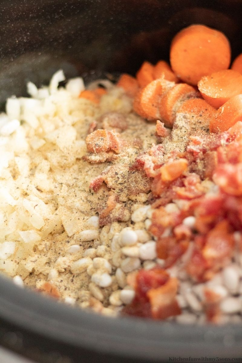 Adding the herbs, spices, and bacon into the slow cooker.