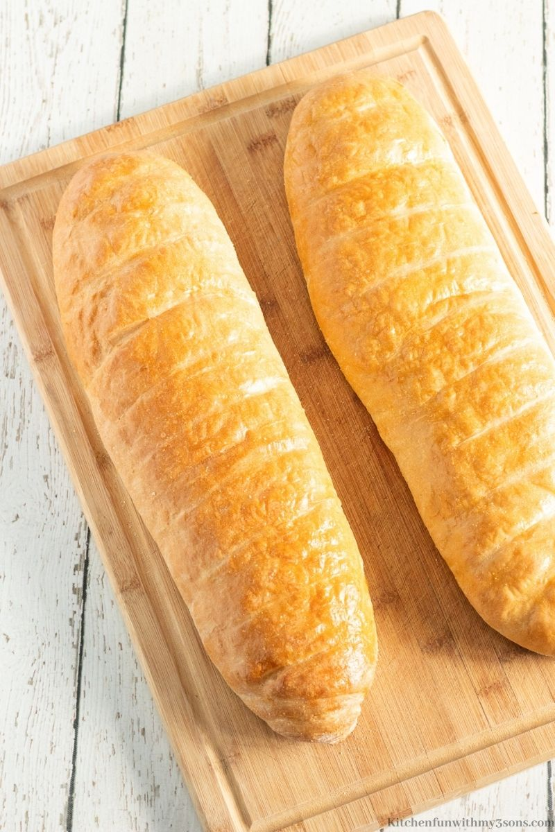 Two loaves of the French bread on a wooden cutting board.