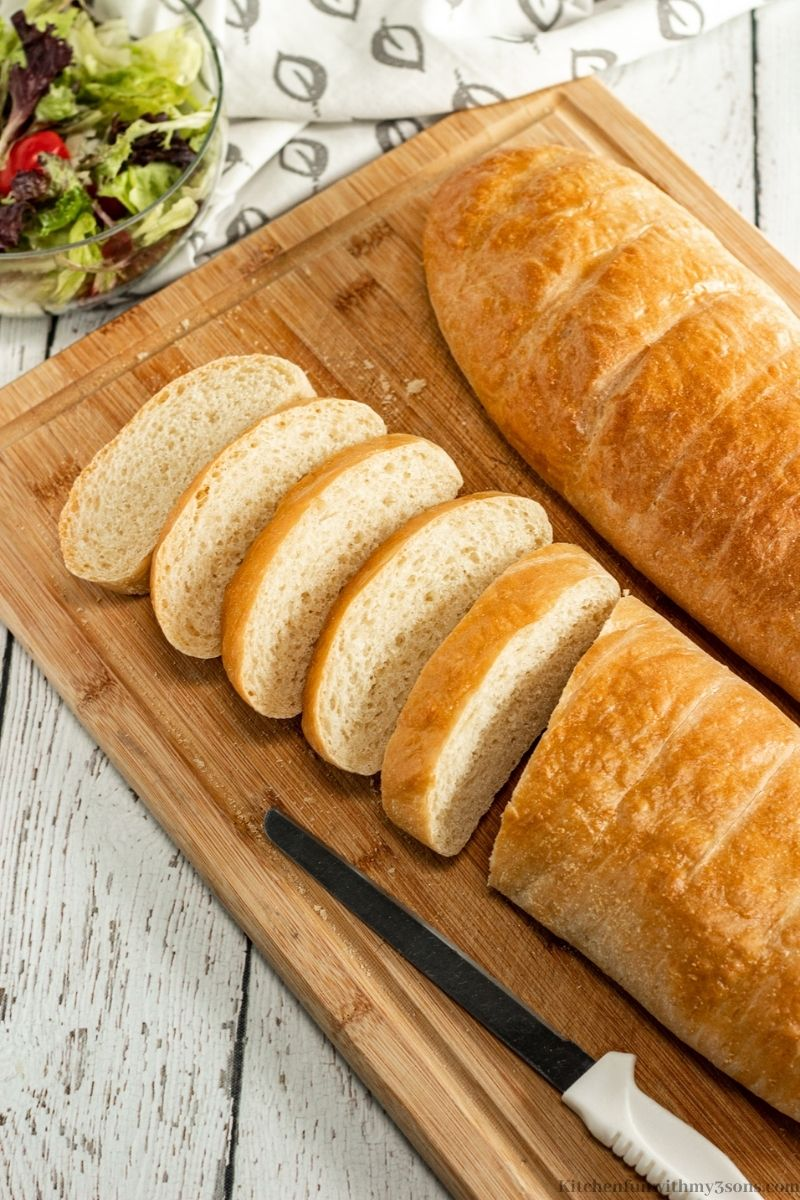 The sliced French bread with a bread knife beside it with a side salad.