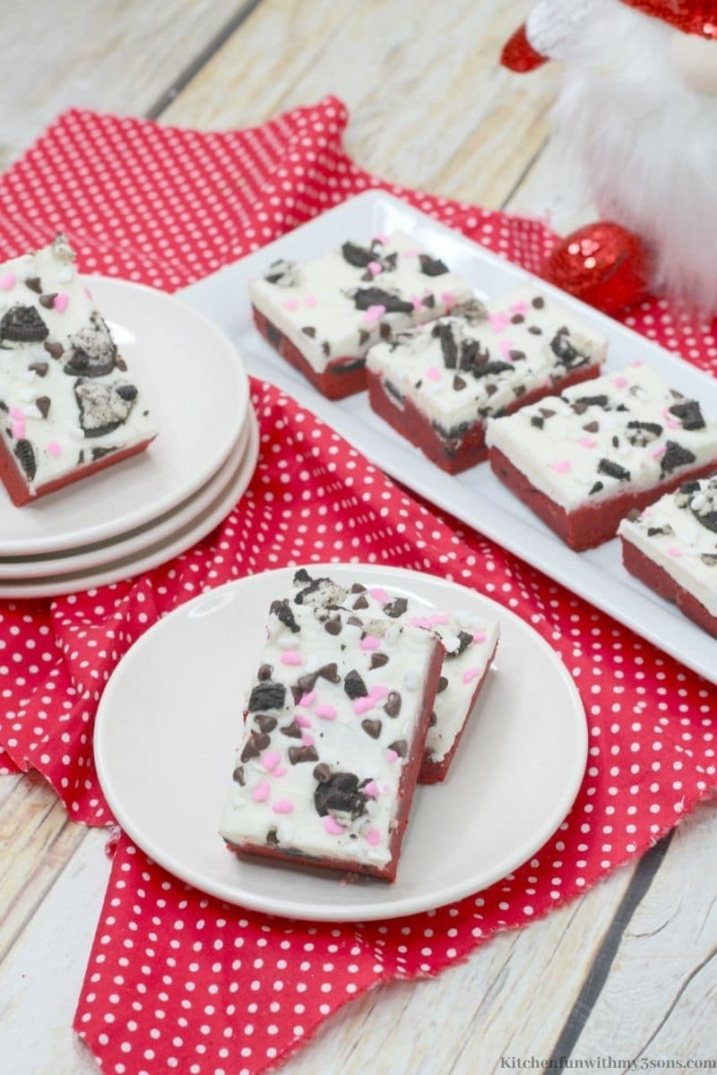 The cookie bars on separate serving dishes on a white and red polka dot cloth.