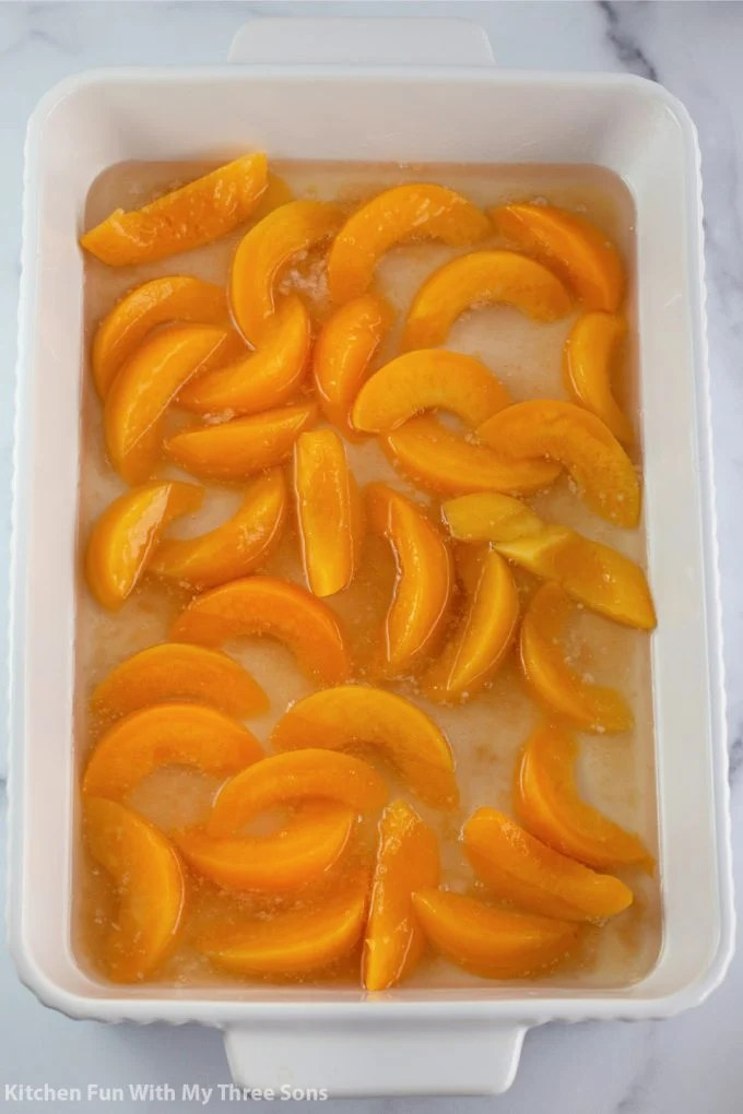 canned peaches in the bottom of the white baking dish.