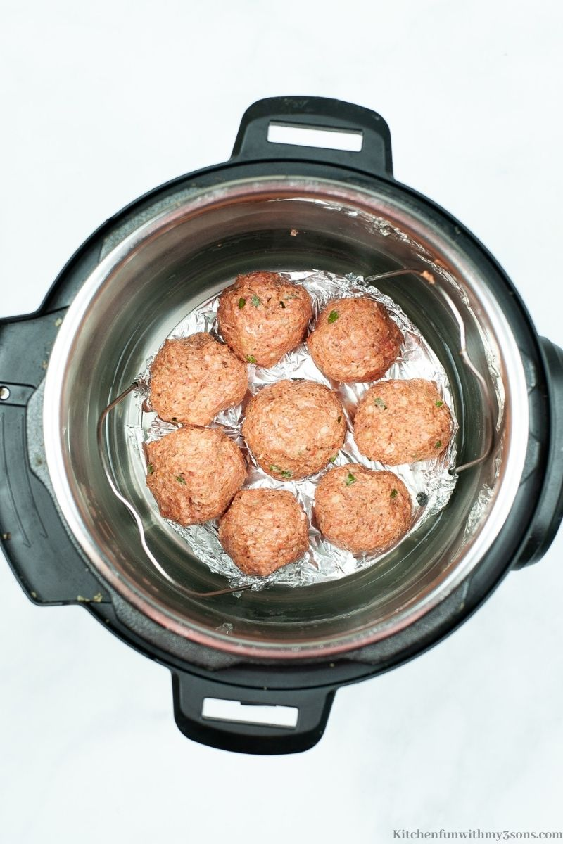 The meatballs on a trivet inside of the Instant Pot.