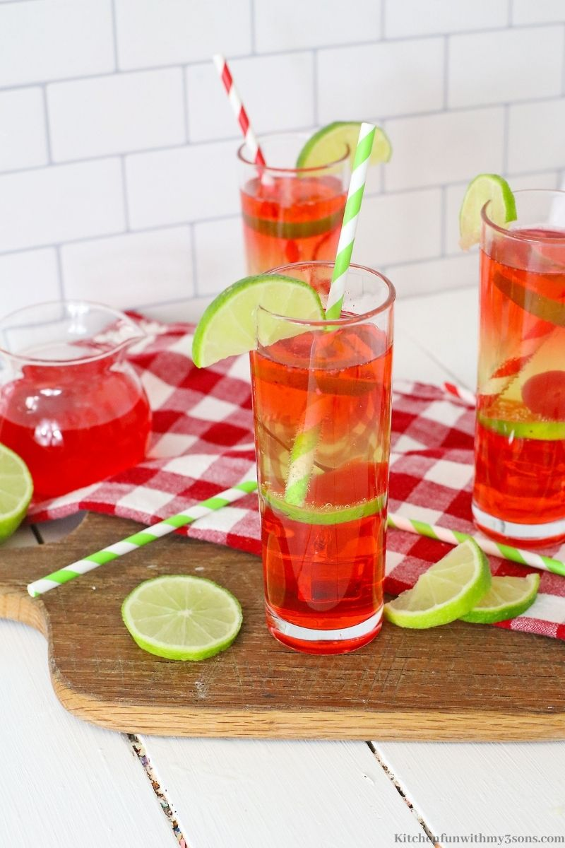 Vodka Cherry Limeade Cocktail on a wooden cutting board with extra limes.