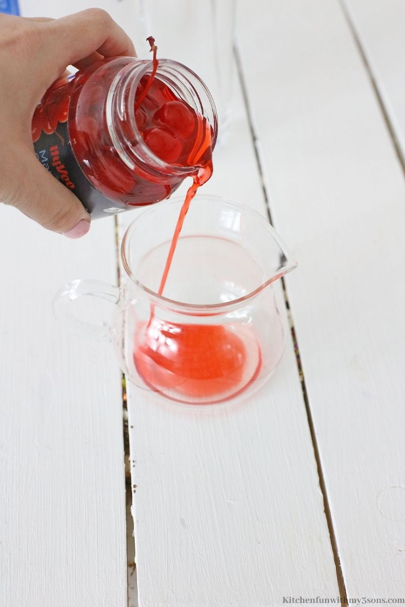 Pouring the cherry juice into a small pitcher.