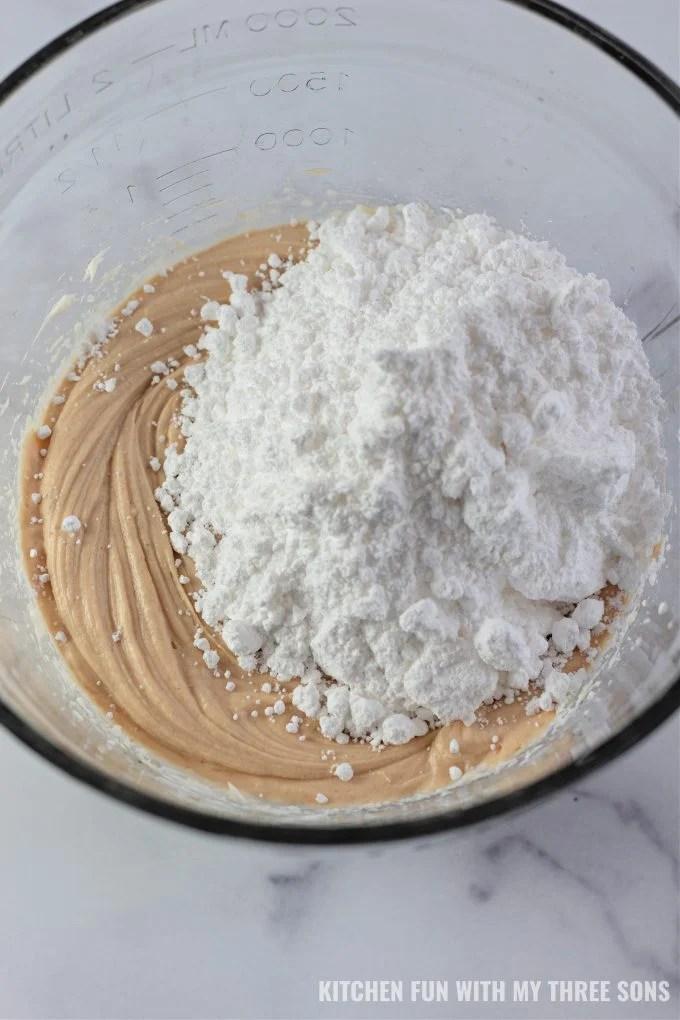 dodajući šećer u prahu u tijesto od maslaca od kikirikija.