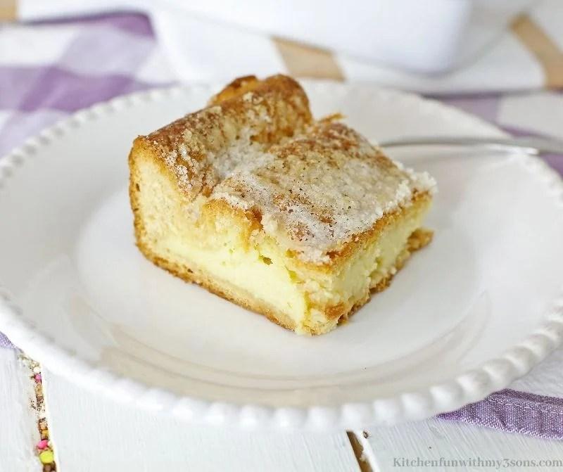 Komad torte od sira na ljubičastoj kockastoj tkanini.