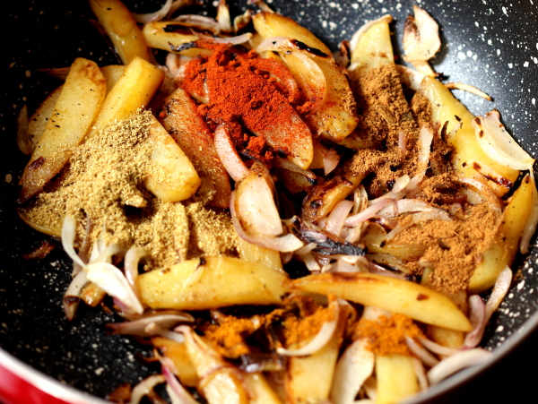The dry masalas are added to the fried potatoes and translucent onions