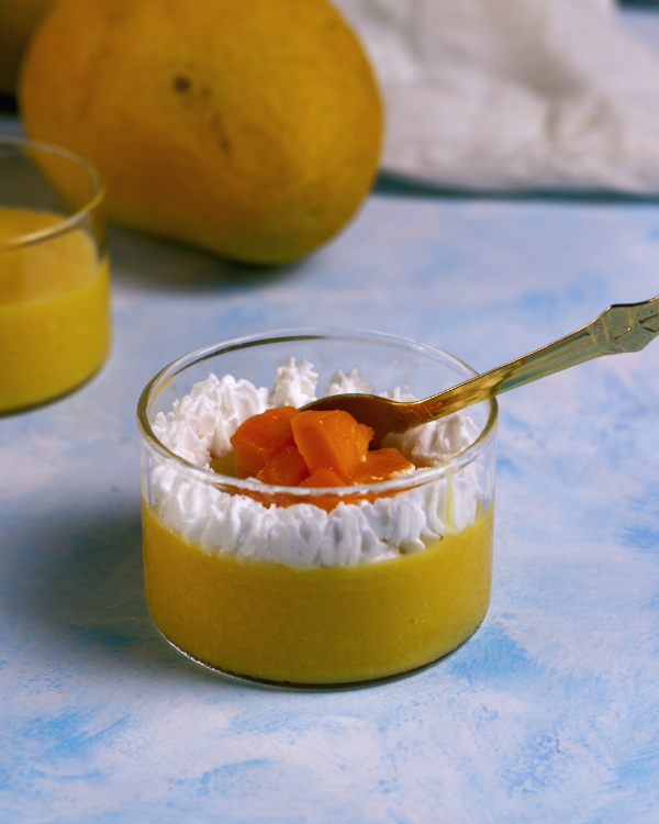 A small serving of mango mousse in a glass dish, decorated with fresh cream and mango pieces