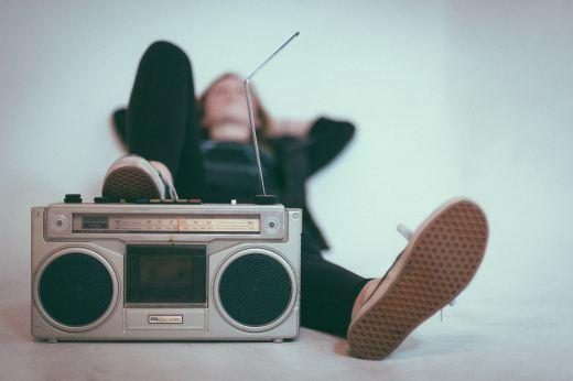 Women lying in white room with her foot on a vintage radio/cassette player.
