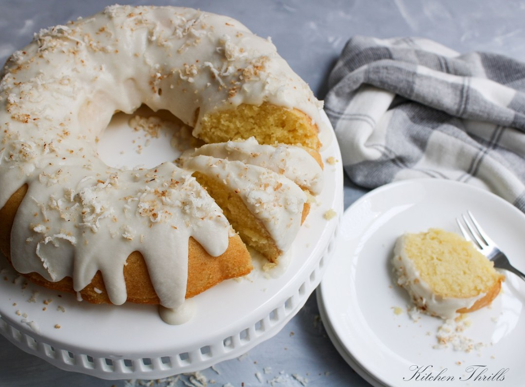 Homemade coconut cake with coconut milk and shredded coconut baked in a bundt pan or a loaf pan and topped with creamy coconut frosting.