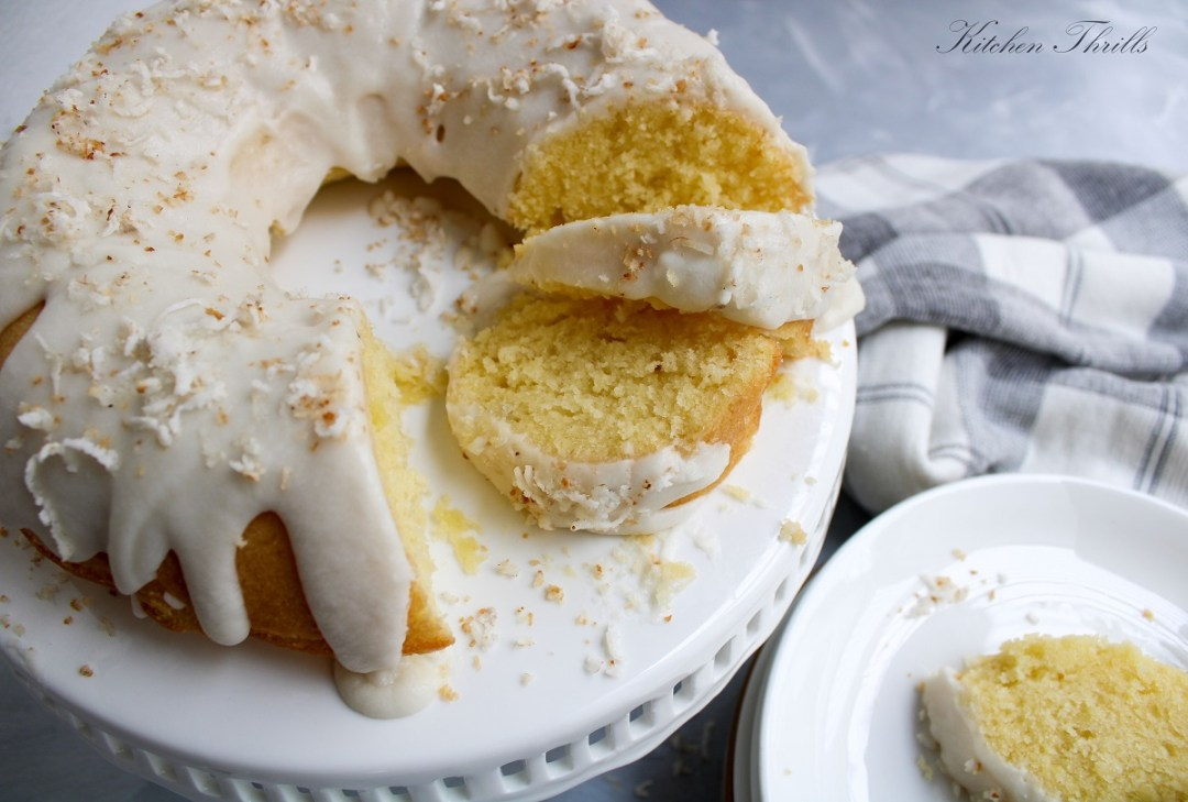 A simple and moist coconut bundt cake with coconut frosting and garnished with toasted coconut.