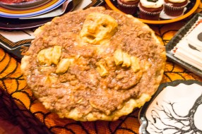 Zombie apple pie with a carved head and hands