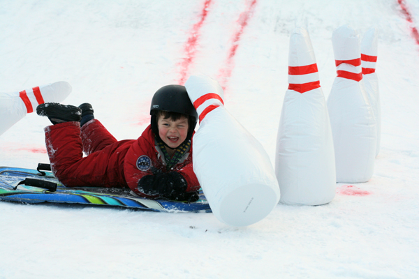 Maddock Currie, 4, happily crashes into the inflatable pins at Dovercourt's annual winter carnival. Photo by Anita Grace.