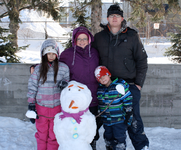 Melissa and Gerard Stiles-O'Connell pose with Maliah, 9, Corey, 5, and the family's snowman creation. Photo by Anita Grace.