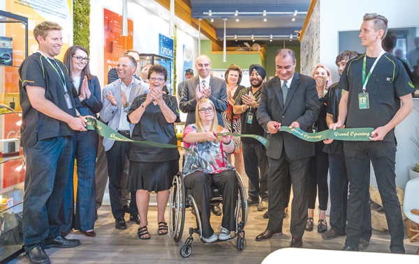 Front row (holding ribbon) from left to right is Josh Vaughan, NAC store manager; Shauna Lidtkie, patient; Gulwant Bajwa, CEO; and Maximillian Weigelt, staff member. Photo by Ted Simpson.