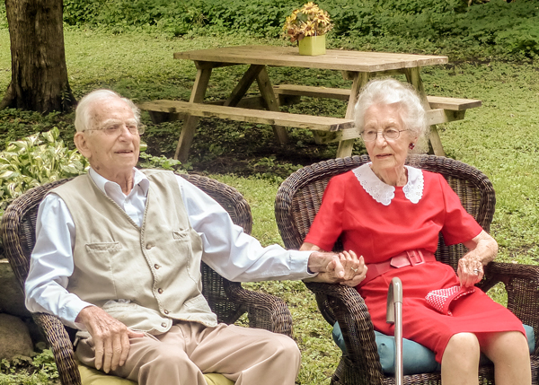 George and Jean Spear on their 72nd anniversary. Jean's red dress and white lace collar is a replica of the dress she was wearing when they first met, many years ago on a dance floor in Kingston-on-Thames. Photo by Judith van Berkom