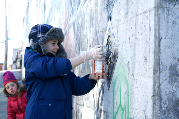 Hintonburg residents, including Noah Parsons, added some finishing touches to the new mural. Photo by Jacob Hoytema