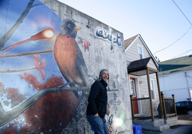 Local street artist Arpi in front of his new mural at the corner of Garland and Lowrey Street. Photo by Jacob Hoytema