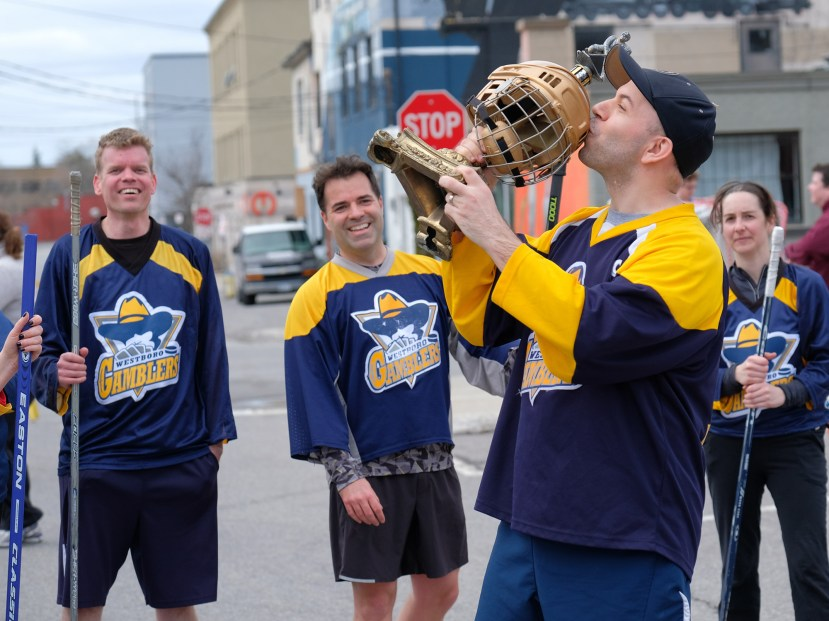 Dave Allston of The Gamblers embraces victory as his teammates – Derek Smith, John Holland, and Kristen Couture – look on.