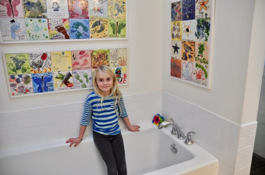 Rose poses with ceramic tile art the kids have made over the years.