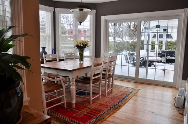 The kitchen opens to a dining area which is surrounded by windows. Photo by Andrea Tomkins