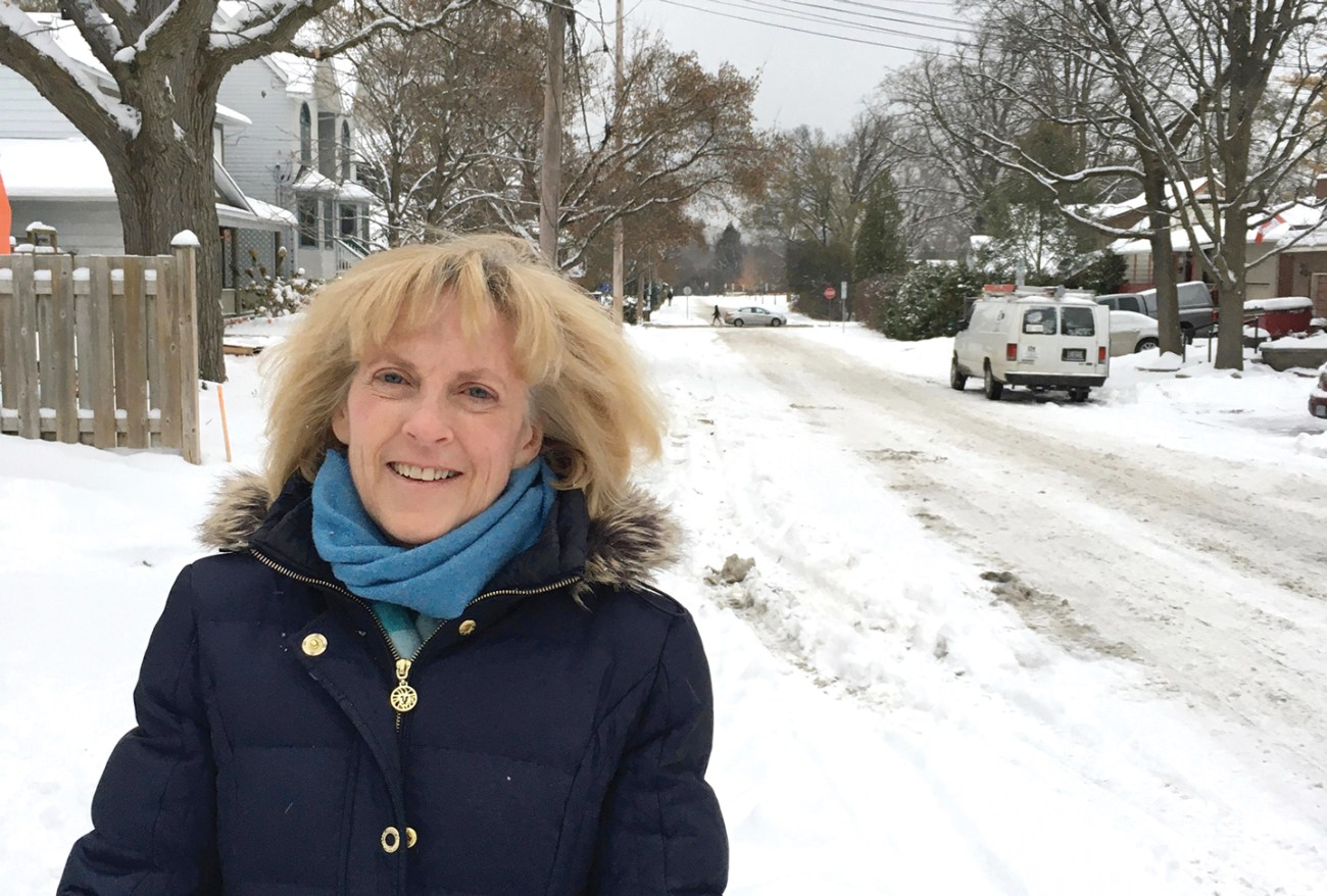 Louise Atkins, a resident of Kitchissippi, stands in front of a snowy street in her neighbourhood.