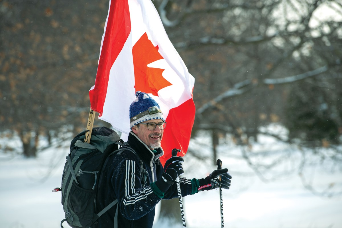 A man dressed for a cross-country skiing outing has a large Canada flag hanging out of his backpack.