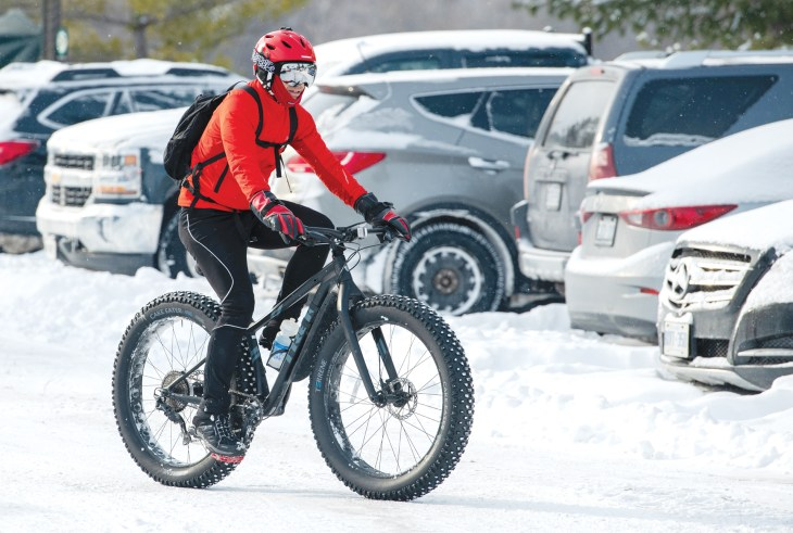 A person rides their fat bike in a snowy parking lot.