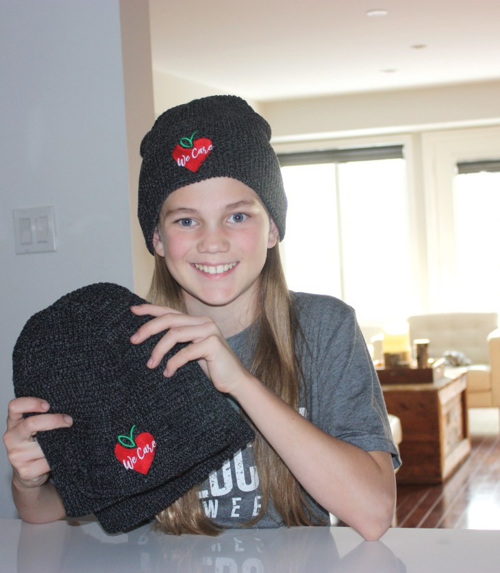 Kylie Hollingsworth, 11, shows off the toques she is selling to raise funds for the Parkdale Food Centre.