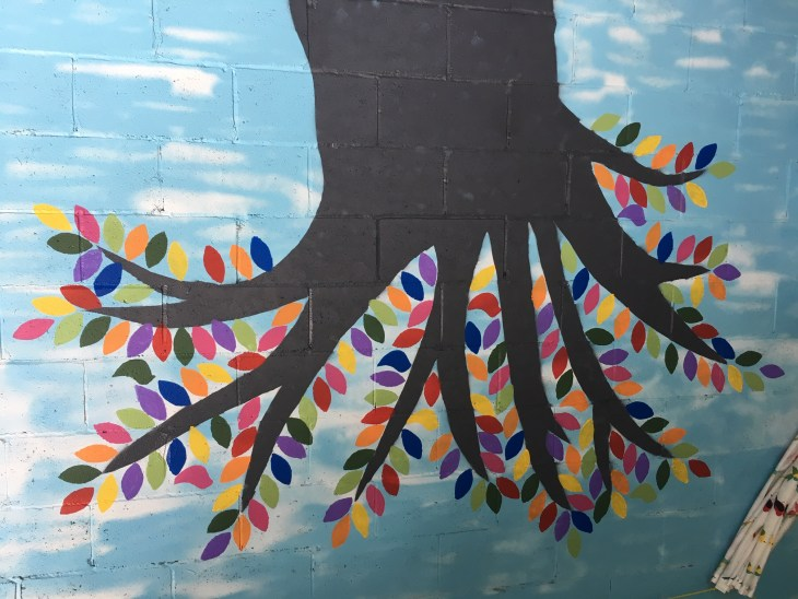 A photo of the colourful tree mural painted by the Thomson family in Hintonburg during the pandemic.