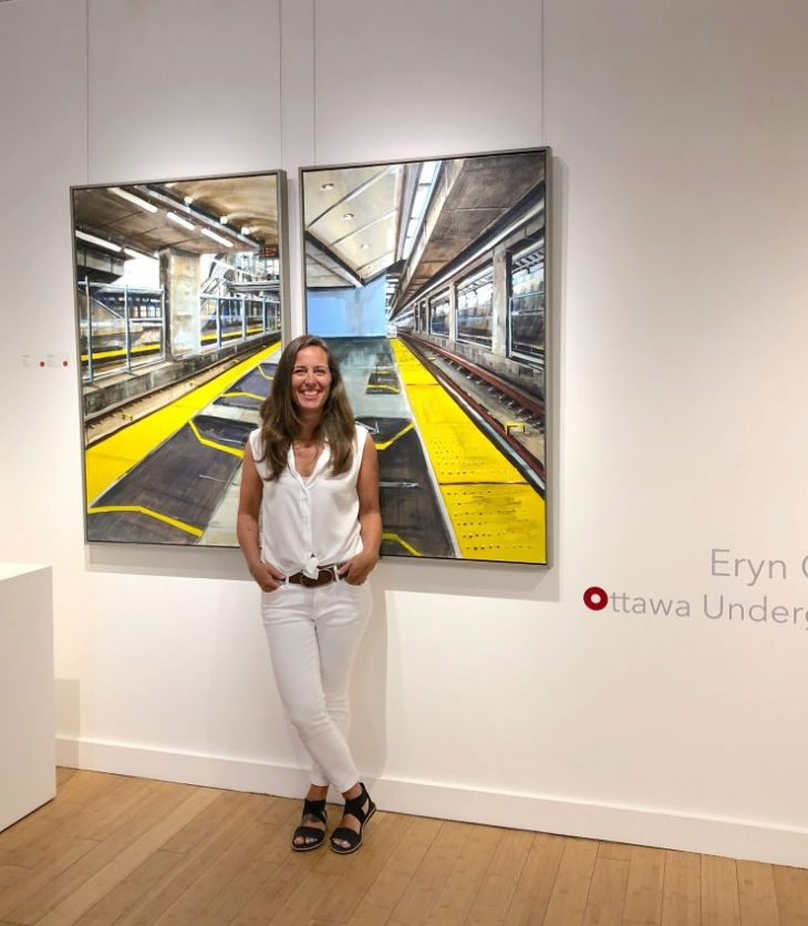 A photo of local Artist Eryn O'Neill standing in front of her newest body of work, Ottawa Underground, on display in Hintonburg.
