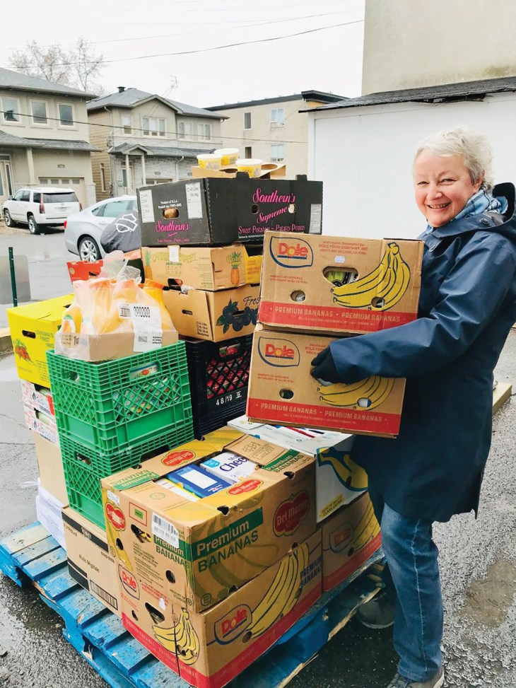 A photo of a volunteer at the Westboro Region Food Bank carrying boxes of food.