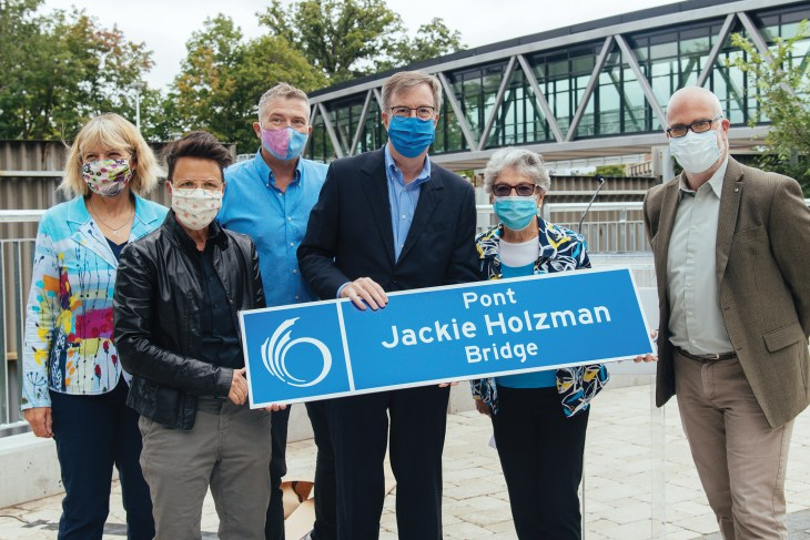 A photo of the mayor, former mayor and current councillors outside of Jackie Holzman Bridge in Ottawa.