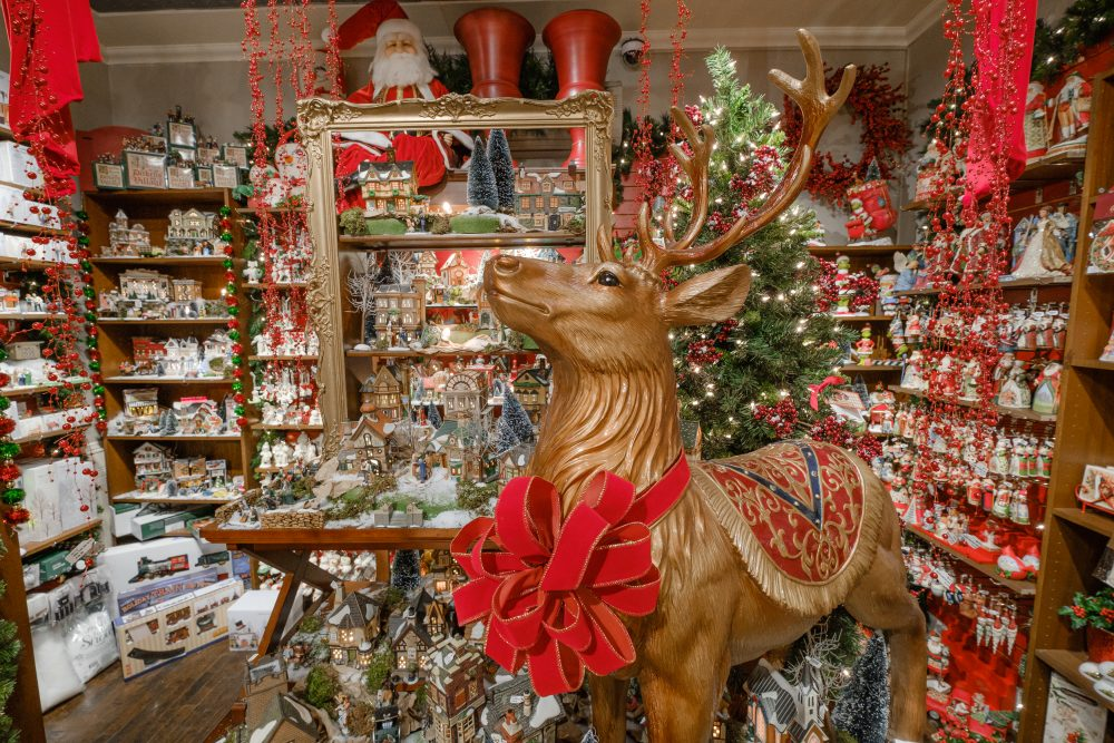 A gold reindeer wearing a red bow stands in Tinseltown in Hintonburg
