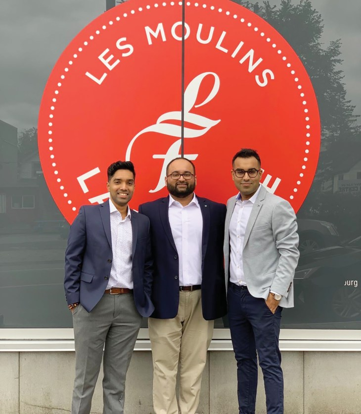 The three co-owners of Les Moulins La Fayette against the company logo in Hintonburg.