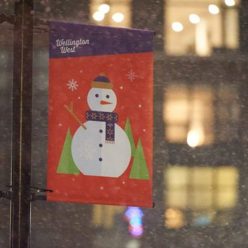A red, green and purple street sign pictures a friendly snowman.