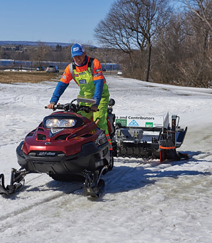 Dave Adams driving a snowmobile on the SJAM trail on a sunny winter day in 2017.