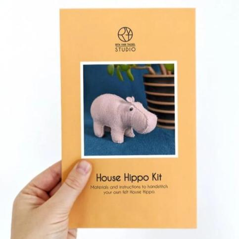 A house hippo sewing kit is being held up in someone's left hand.
