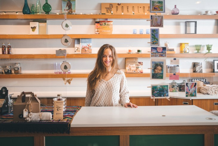 Jessie Lyon stands in front of shelves at at the cash register in Pokoloko X Cloud Forest.