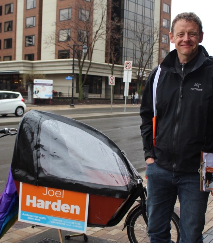 Joel Harden stands on the street next to a campaign sign on a bike in Ottawa