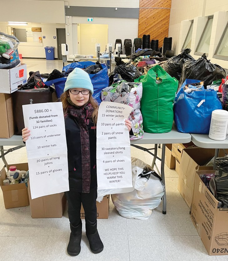An 8-year-old girl stands in front of a table with donated items piled on top of it at the Tom Brown Arena Respite Centre